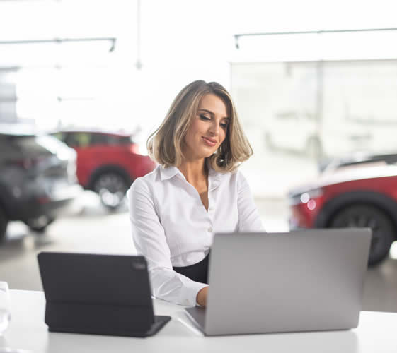Lady working on the front desk in car showroom